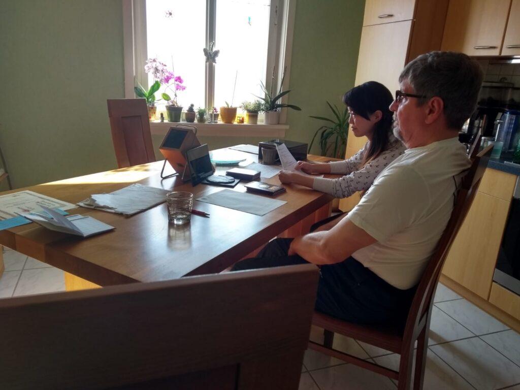 Jogi und Maki sitzen vor einem Tablet und nehmen die Gelbgurtprüfung ab