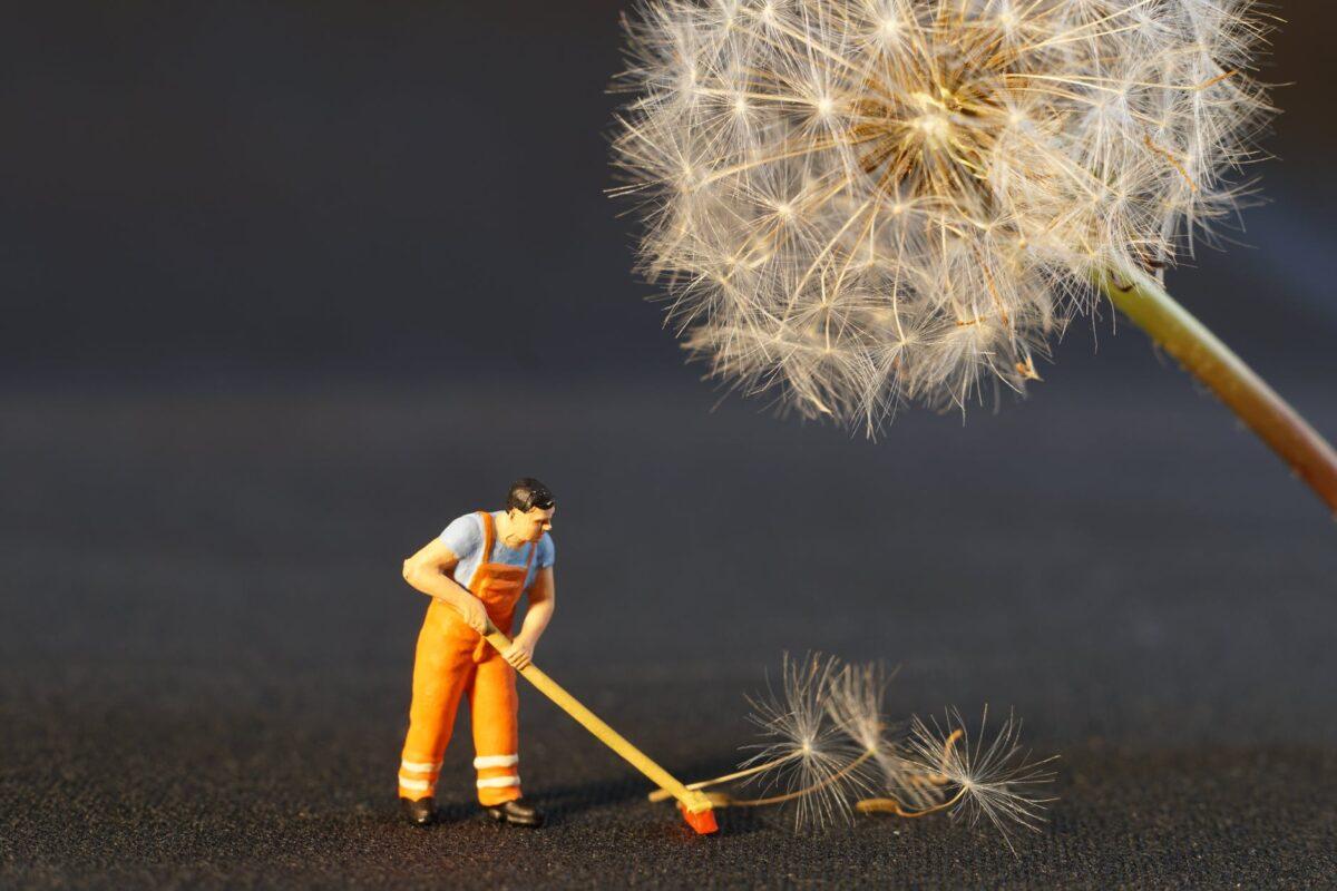 shallow focus photo of man holding floor brush ceramic figurine